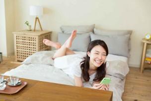 無線LANルーター新しく買って、超快適にスマホでWi-Fi接続している女性