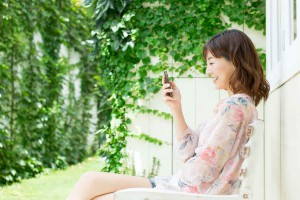 庭でスマホを使う若い女性