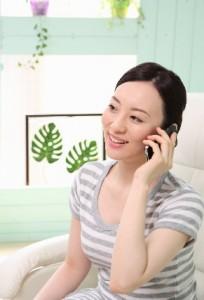 電話でプロバイダーに連絡する女性