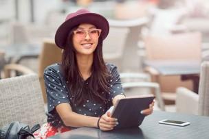 ポケットwifiの新機種とタブレットを使って、カフェでネットを楽しむ美女