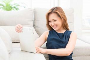BIGLOBEのWiMAX2+をタブレットで調べる女性